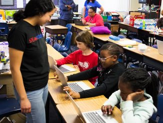 An instructor stops to see if she can help some young girls with their computer assignment during an afternoon at STEAM:Coders. The program encourages at-risk students to pursue careers in science, technology, engineering, the arts or math. (Courtesy photo)