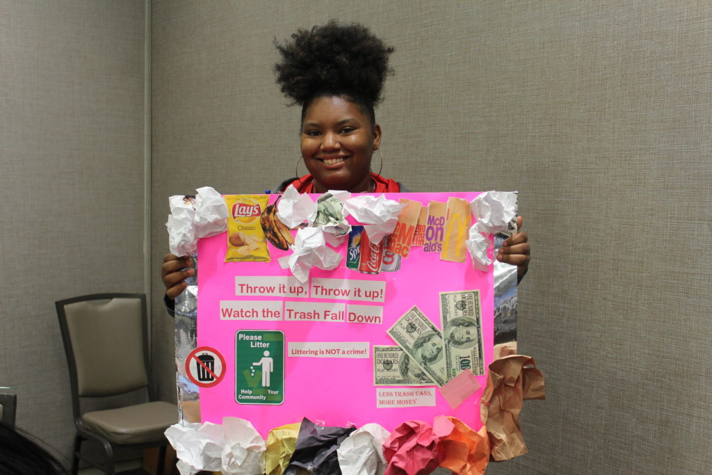A student holds up her poster in favor for there being no law against littering. (Ariel Worthy/The Birmingham Times)